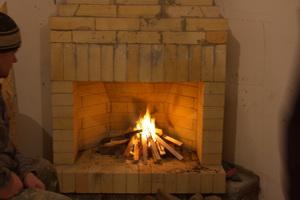 Розжиг огня. Угловой камин в каркасном доме.